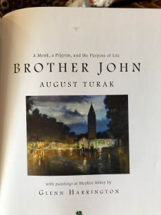 "This shows the inner page of the book. Title of the book: ""Brother John: A monk, a pilgrim, and the purpose of life."" Beneath is a picture of the Abbey of Mepkin, a tall spire of the church with the warm glow of buildings underneath it."